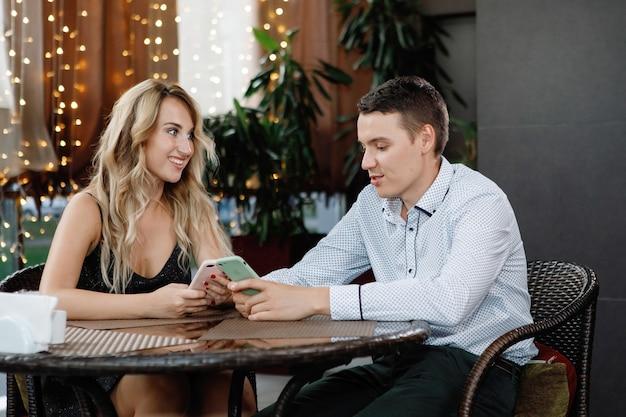 Mężczyzna i kobieta ze smartfonami przy stole w kawiarni
