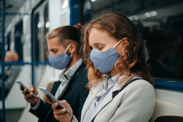 Mężczyzna i kobieta ze smartfonami siedzą w wagonie metra