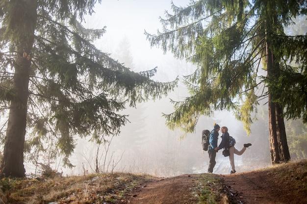 Mężczyzna i kobiety backpackers cieszy się na mgłowym lasowym halnym śladzie