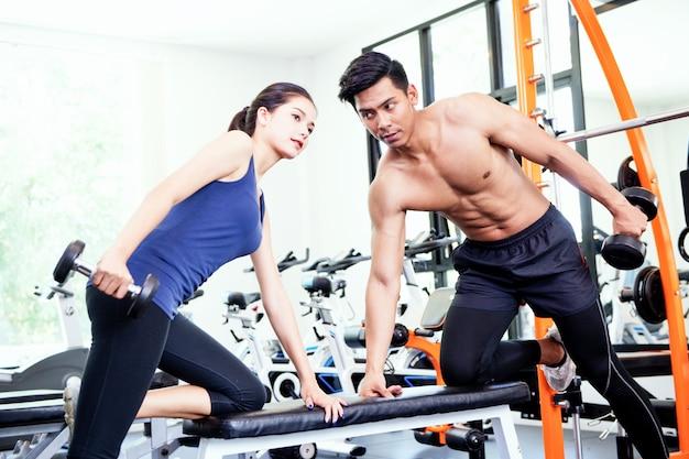 Mężczyzna i kobiety pracujące w siłowni razem