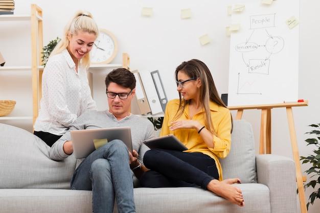 Mężczyzna i kobiety siedzi na kanapie i pracuje na laptopie