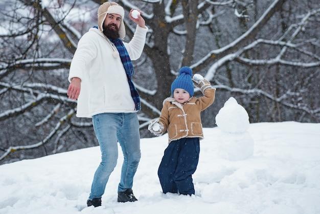 Mężczyzna i mały chłopiec robi bałwana odkryty