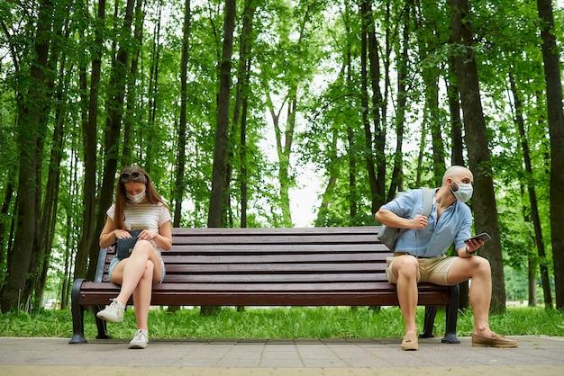 Mężczyzna i młoda kobieta siedzą na przeciwległych końcach ławki, zachowując odległość od siebie, aby uniknąć rozprzestrzeniania się koronawirusa.