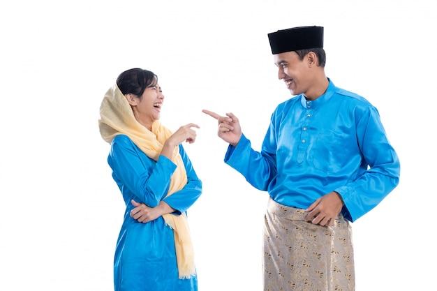 Mężczyzna i muzułmańska kobieta opowiada nad bielem