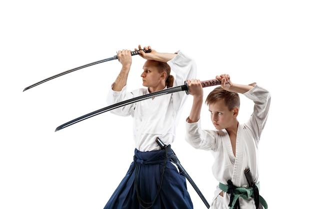 Mężczyzna i nastolatek walczą na treningu aikido w szkole sztuk walki. pojęcie zdrowego stylu życia i sportu. bojownicy w białym kimonie na białej ścianie. karate mężczyźni o skupionych twarzach w mundurach.