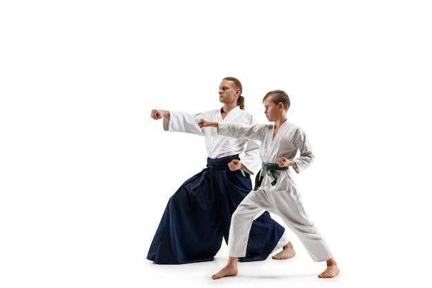 Mężczyzna i nastolatek walczą na treningu aikido w szkole sztuk walki. pojęcie zdrowego stylu życia i sportu. bojownicy w białym kimonie na białej ścianie. mężczyźni karate o skupionych twarzach w mundurach.