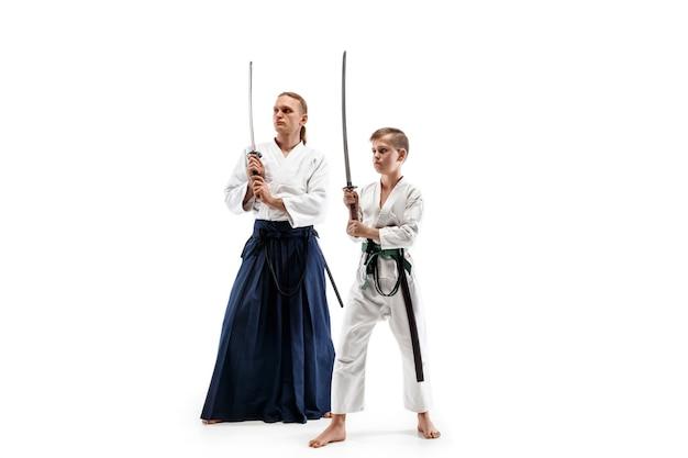 Mężczyzna i nastolatek walczą na treningu aikido w szkole sztuk walki