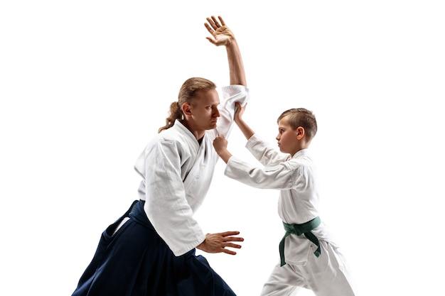 Mężczyzna i nastolatek walczący podczas treningu aikido w szkole sztuk walki. koncepcja zdrowego stylu życia i sportu. bojownicy w białym kimonie na białej ścianie. karate mężczyźni o skoncentrowanych twarzach w mundurach.