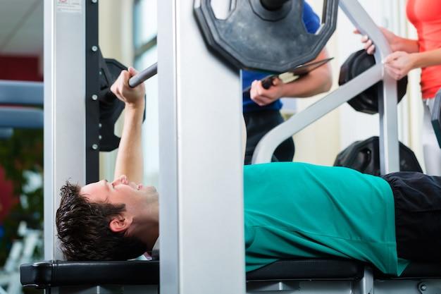 Mężczyzna i osobisty trener w siłowni