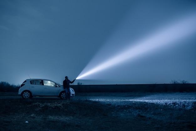 Mężczyzna i pies eksplorują pole nocą, nocą rozjaśniają niebo pochodnią