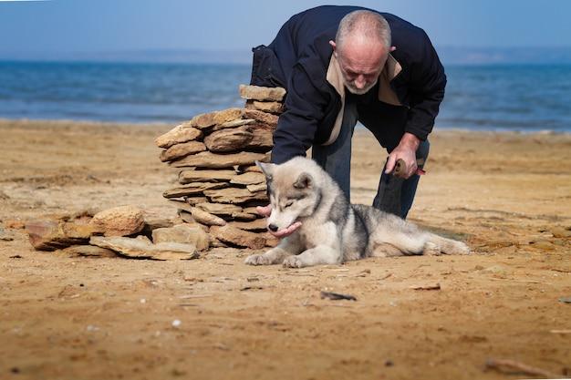 Mężczyzna i pies husky chodzić w parku.