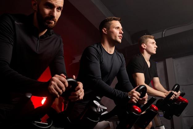 Mężczyzna i przyjaciele na rowerze fitness na siłowni podczas treningu, czekają, pracowici, silni, muskularni mężczyźni w odzieży sportowej