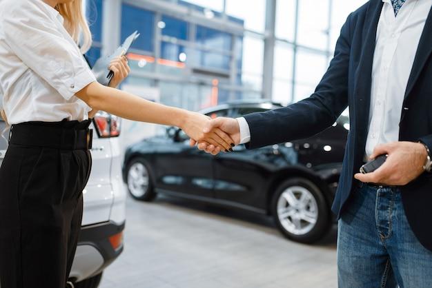 Mężczyzna i sprzedawczyni podają sobie ręce w salonie samochodowym. klient i sprzedawca w salonie samochodowym, mężczyzna kupujący transport, firma dealera samochodowego dealer