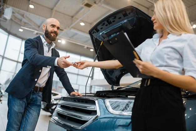 Mężczyzna i sprzedawczyni wybierając auto w salonie samochodowym. klient i sprzedawca w salonie samochodowym, mężczyzna kupujący transport, firma dealera samochodowego