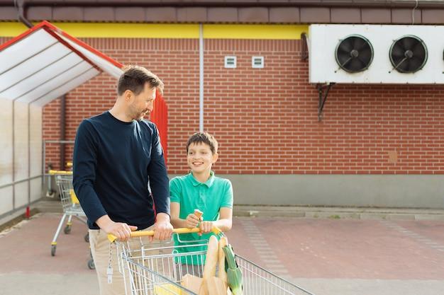 Mężczyzna i syn poszli razem na zakupy i idą do samochodu z wózkiem na zakupy, spędzają razem czas, koncepcja samotnego ojca