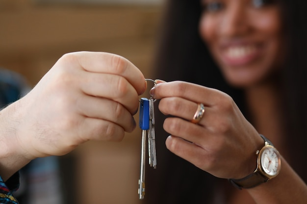 Mężczyzna i szczęśliwa kobieta trzymać klucze w raki