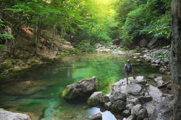Mężczyzna i wiosna jezioro w zielonym lesie