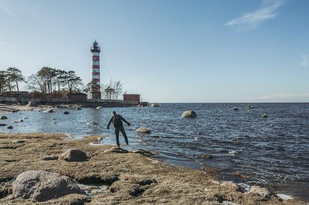 Mężczyzna idący po kamienistym wybrzeżu obok latarni morskiej.