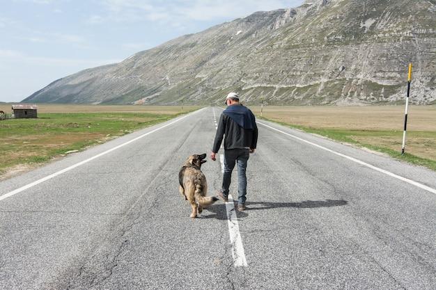 Mężczyzna idzie na drodze z psem w górach