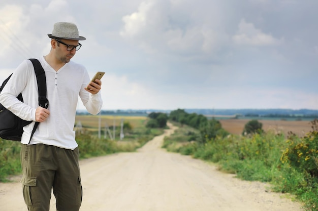 Mężczyzna idzie polną drogą. autostopowicz w całym kraju. mężczyzna zatrzymuje przejeżdżający samochód.