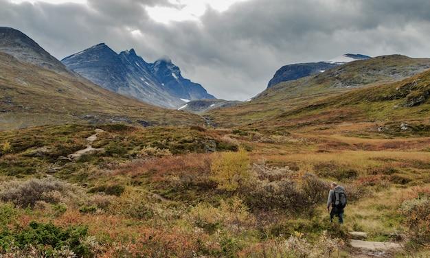 Mężczyzna idzie w kierunku gór hurrungane w jotunheimen, norwegia