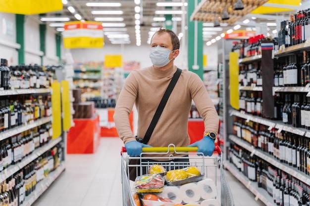 Mężczyzna idzie w supermarkecie z wózkiem na zakupy z towarami, nosi maskę medyczną i gumowe rękawiczki, kończy się jedzenie z powodu koronawirusa