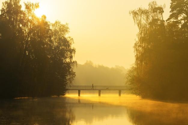 Mężczyzna idzie z psem przez most o wschodzie słońca.