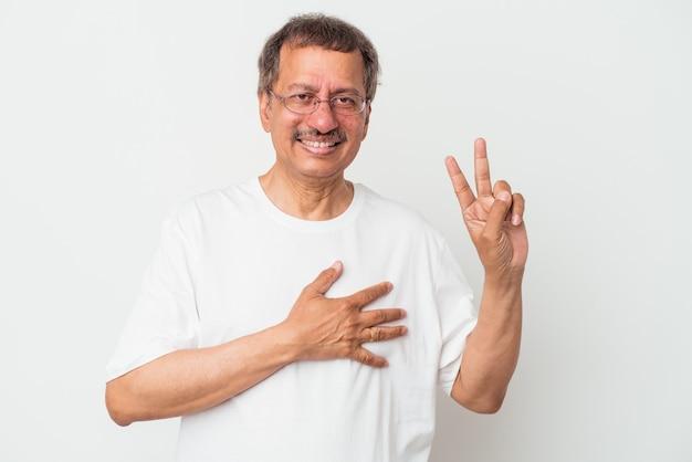 Mężczyzna indian w średnim wieku na białym tle składa przysięgę, kładąc rękę na klatce piersiowej.