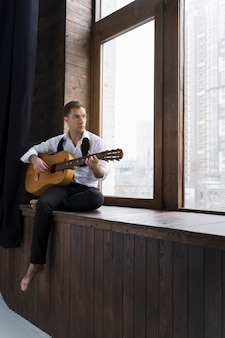 Mężczyzna indoors bawić się gitara instrument