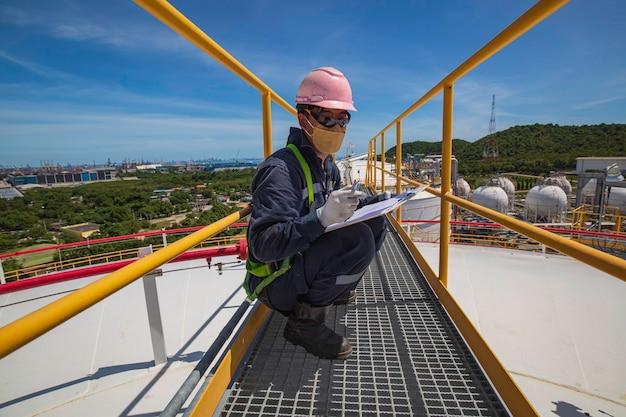 Mężczyzna inspekcja wizualna dachu zbiornika oleju tło miasta i błękitne niebo.