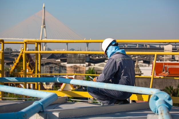 Mężczyzna inspekcja wizualna zbiornika na dachu zbiornika oleju w tle miasto i błękitne niebo