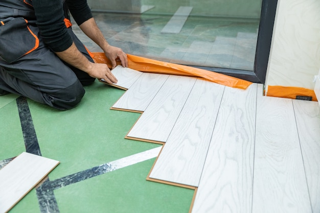 Mężczyzna instalujący nową drewnianą podłogę laminowaną