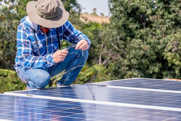 Mężczyzna instalujący panele słoneczne connect power na dachu domu w celu uzyskania alternatywnej, bezpiecznej energii fotowoltaicznej. moc z natury energia słoneczna generator ogniw słonecznych oszczędza ziemię