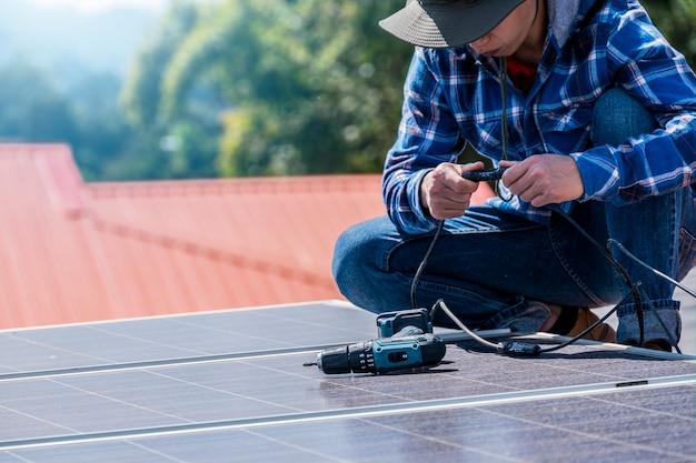 Mężczyzna instalujący panele słoneczne na dachu domu w celu zapewnienia bezpiecznej energii fotowoltaicznej alternatywnej energii.
