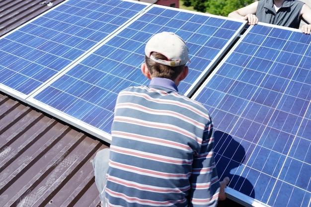 Mężczyzna instaluje alternatywne energii fotowoltaiczne panele słoneczne na dachu