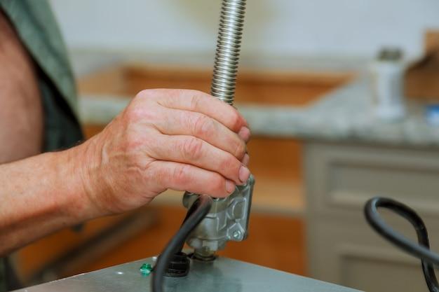Mężczyzna instaluje kuchenkę gazową w kuchni.