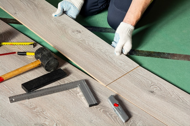 Mężczyzna instaluje nowe podłogi laminowane