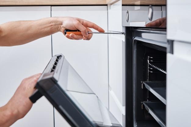 Mężczyzna instaluje piekarnik elektryczny w kuchni