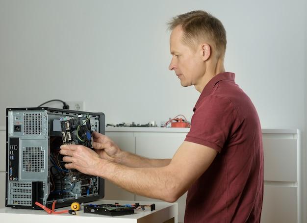 Mężczyzna instaluje płytę główną w obudowie komputera stacjonarnego.