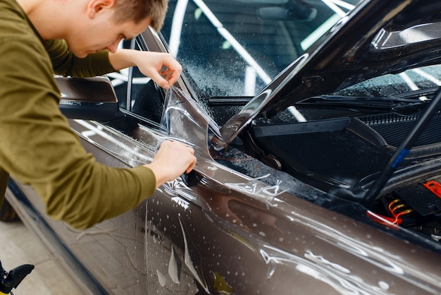 Mężczyzna instaluje przezroczystą folię ochronną na masce samochodu. montaż powłoki chroniącej lakier samochodu przed zarysowaniami. nowy pojazd w garażu, tuning