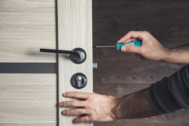 Mężczyzna instaluje śrubokrętem część drewnianych drzwi
