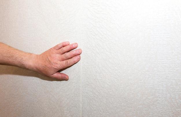 Mężczyzna instaluje tapetę. poziomowanie ściany. prace remontowo-remontowe remontowe w mieszkaniu. renowacja w pomieszczeniu.