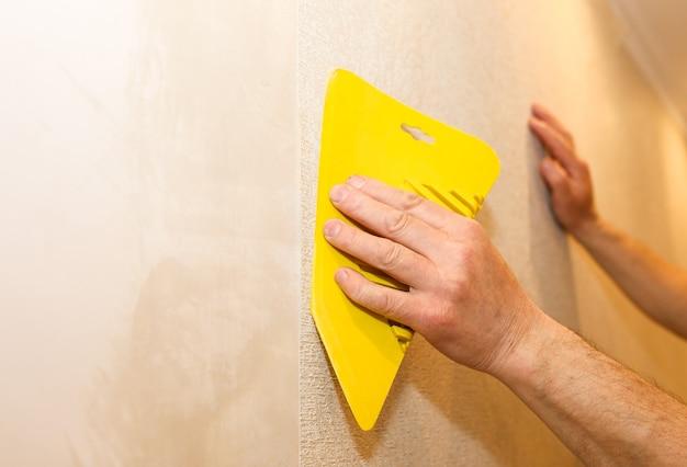 Mężczyzna instaluje tapetę za pomocą skrobaka. poziomowanie ściany. prace remontowo-remontowe remontowe w mieszkaniu. renowacja w pomieszczeniu.