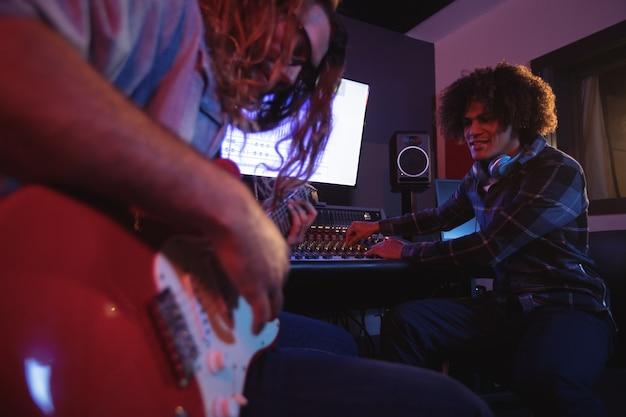 Mężczyzna inżynier dźwięku gra na gitarze elektrycznej