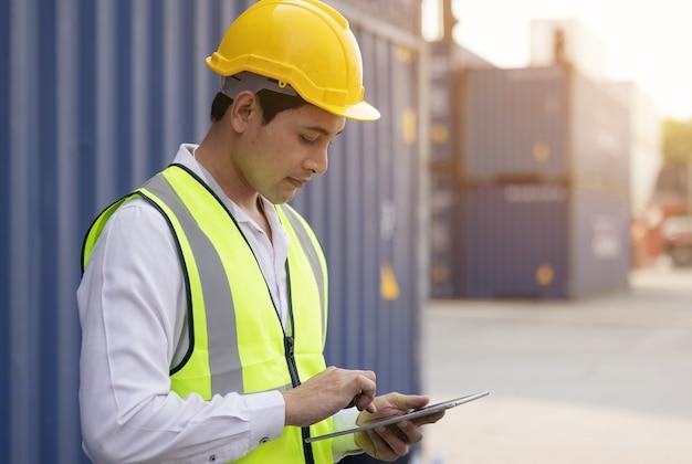 Mężczyzna inżynier, inspekcja pracownika sprawdzająca pojemnik za pomocą tabletu.