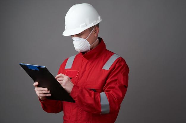 Mężczyzna inżynier, pracownik budowlany jest ubranym twarzy maskę