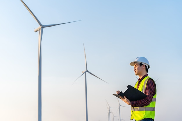 Mężczyzna inżynier pracuje i pisze w schowku przed farmą turbin wiatrowych