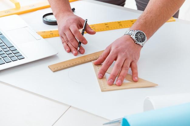 Mężczyzna inżynier pracuje nad rysunkami i projektami