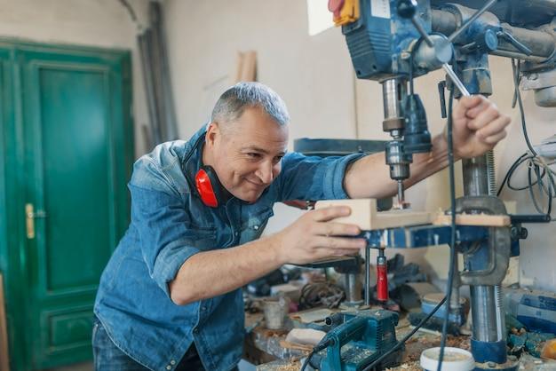 Mężczyzna inżynier stoi blisko saw maszyny robić meble przy cieślami warsztatowymi.