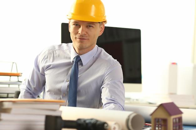 Mężczyzna inżynier w żółtym kasku siedzi w biurze
